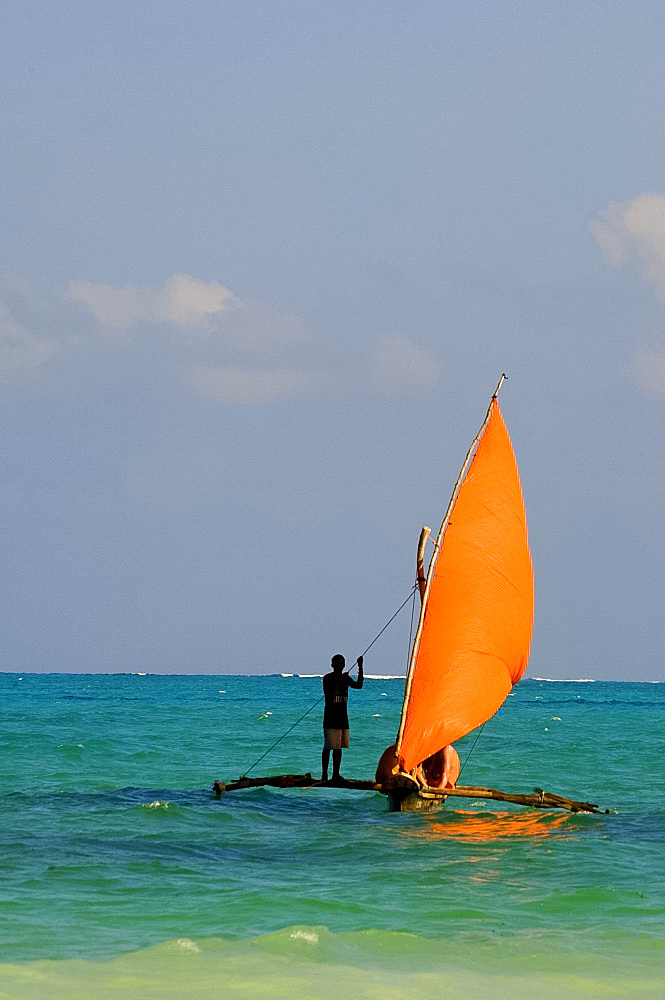 A traditional wooden dhow with an orange sail, Paje, Zanzibar, Tanzania, East Africa, Africa