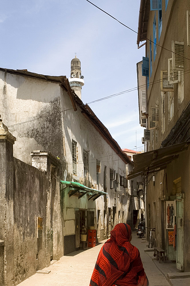 A woman in a colourful headscarf walking down a narrow street with a mosque minaret in Stone Town, Zanzibar, Tanzania, East Africa, Africa