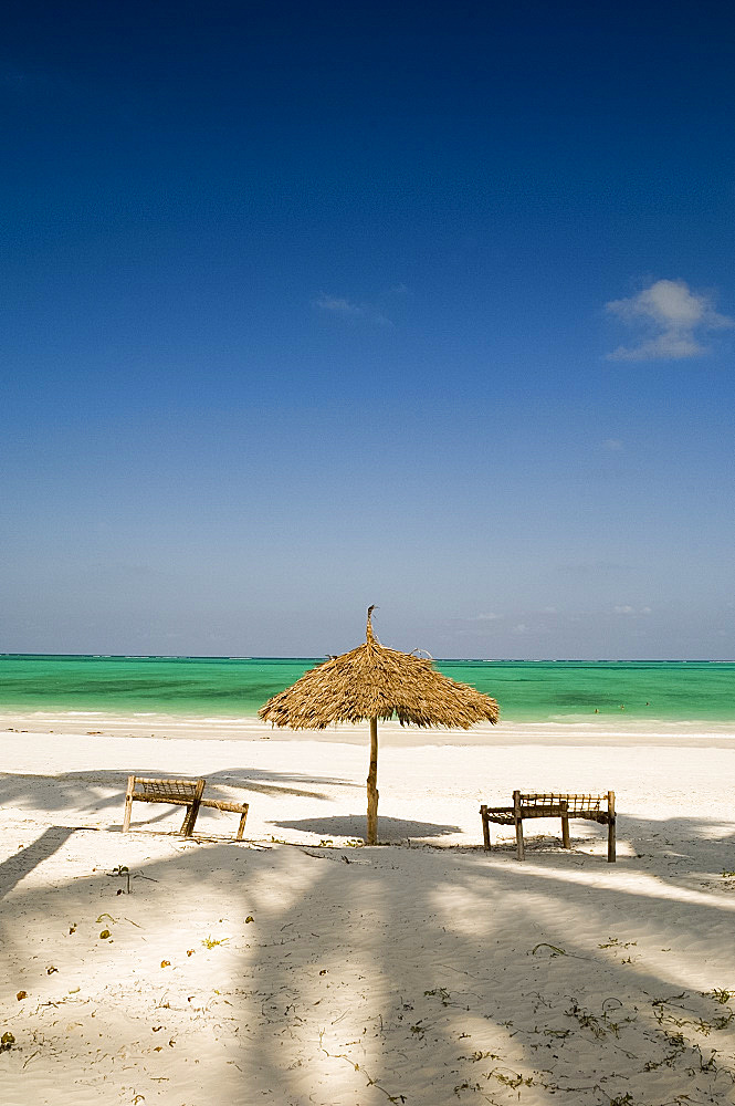 A thatched umbrella and traditional coconut wood sunbeds on Paje Beach, Paje, Zanzibar, Tanzania, East Africa, Africa