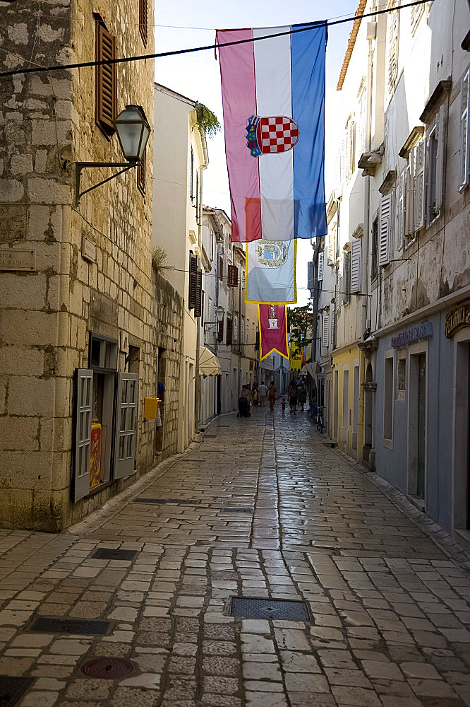 Medieval flags and stone paving in the main shopping street, Srednja Street, Rab Town, island of Rab, Kvarner region, Croatia, Europe