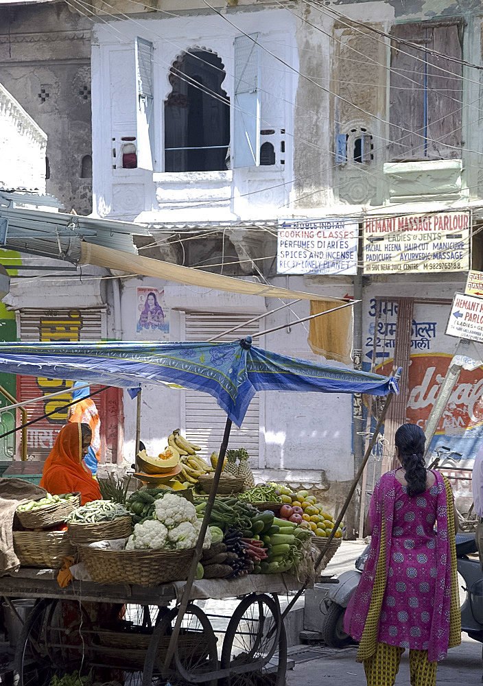 A woman selling fruit and vegetables at a stand in the old part of Udaipur, Rajasthan, India, Asia