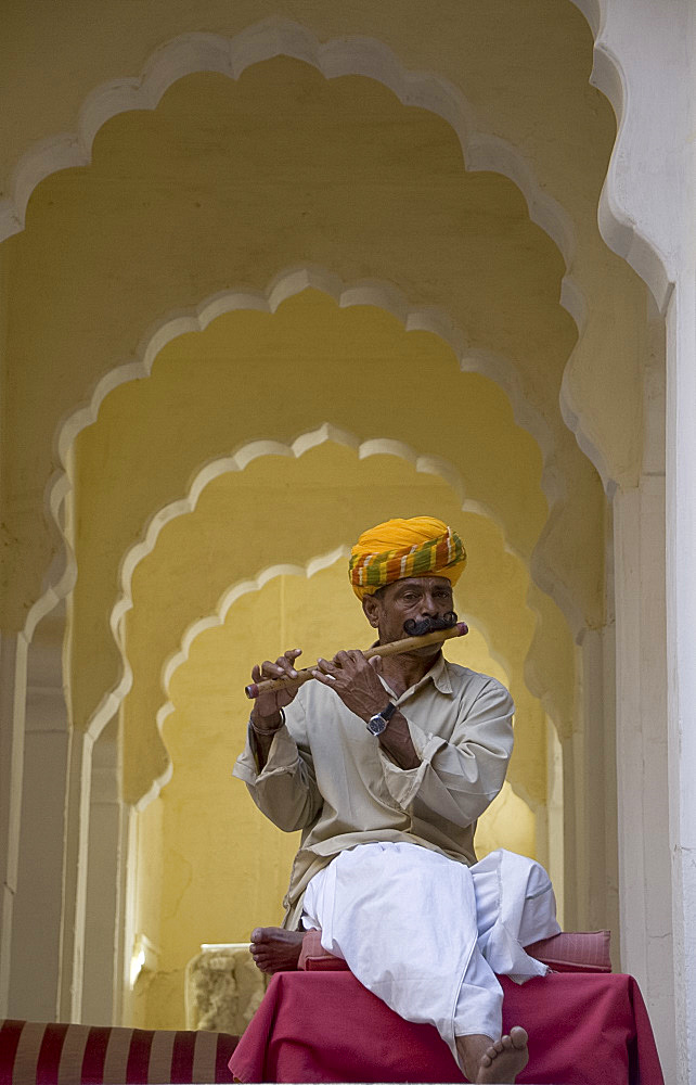A man in traditional Indian dress playing a wooden flute at the Meherangarh Fort in Jodhpur, Rajasthan, India, Asia