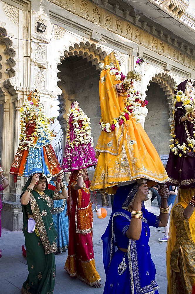 Sari clad women carrying idols at the Mewar Festival in Udaipur, Rajasthan, India, Asia