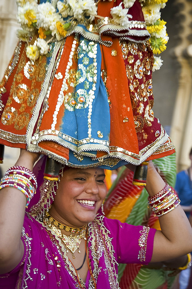 Sari clad woman carrying idol at the Mewar Festival in Udaipur, Rajasthan, India, Asia