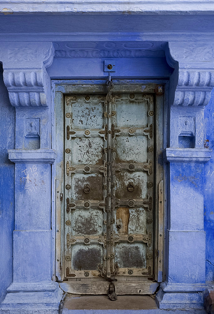 An old metal door of a traditional blue painted house in Jodhpur, Rajasthan, India, Asia