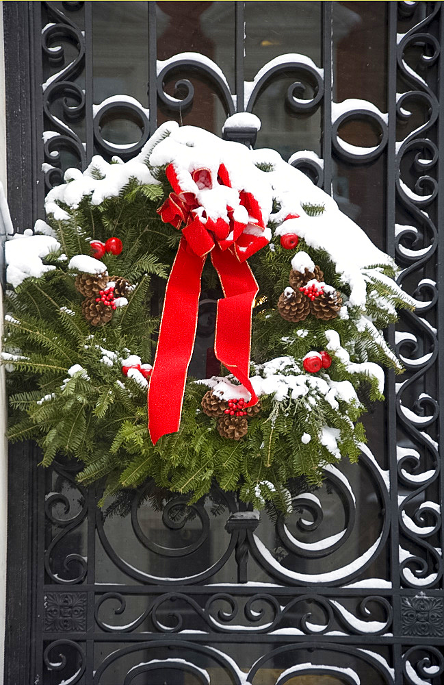 A snow covered Christmas wreath on a door on the East Side of Manhattan, New York City, New York State, United States of America, North America