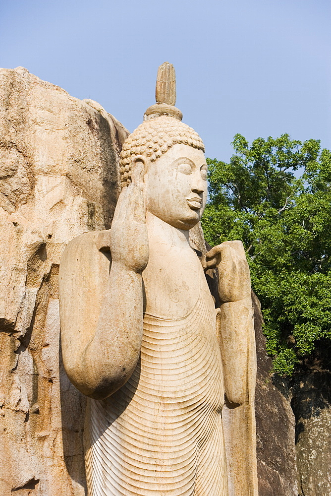 Giant standing statue of the Buddha, his right hand raised in blessing, the left hand lifting the robe symbolising reincarnation, Aukana, Sri Lanka, Asia