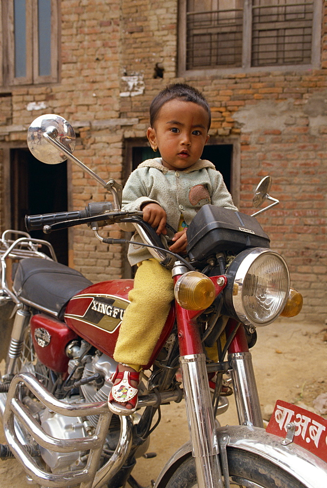 Portrait of young child sitting on motorcycle, Kathmandu, Nepal, Asia