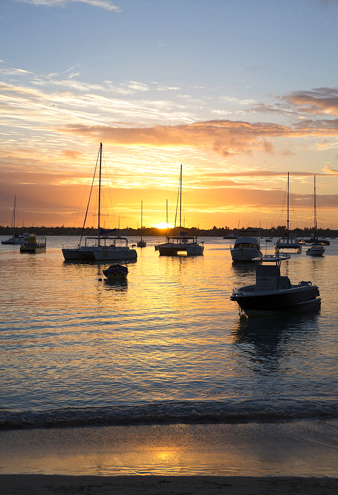 Sunset over the Indian Ocean with boats in silhouette on the calm water off the beach at Gran Baie on the north coast of Mauritius, Indian Ocean, Africa