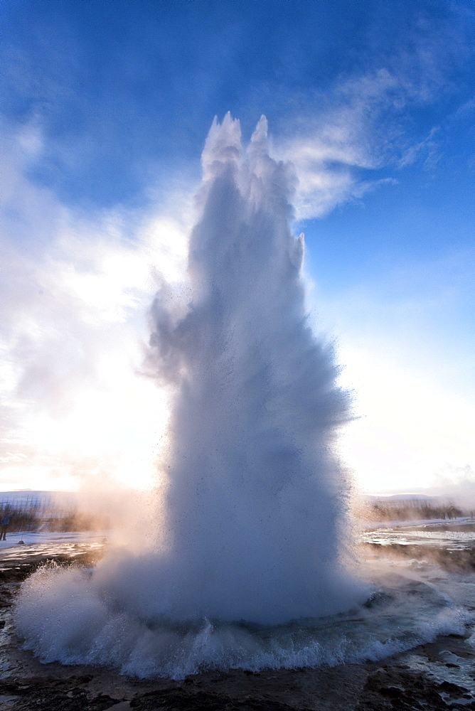 Strokkur Geysir erupting at sunrise on a freezing winter's morning against the colourful sky, Geysir, Haukardalur Valley, Iceland, Polar Regions