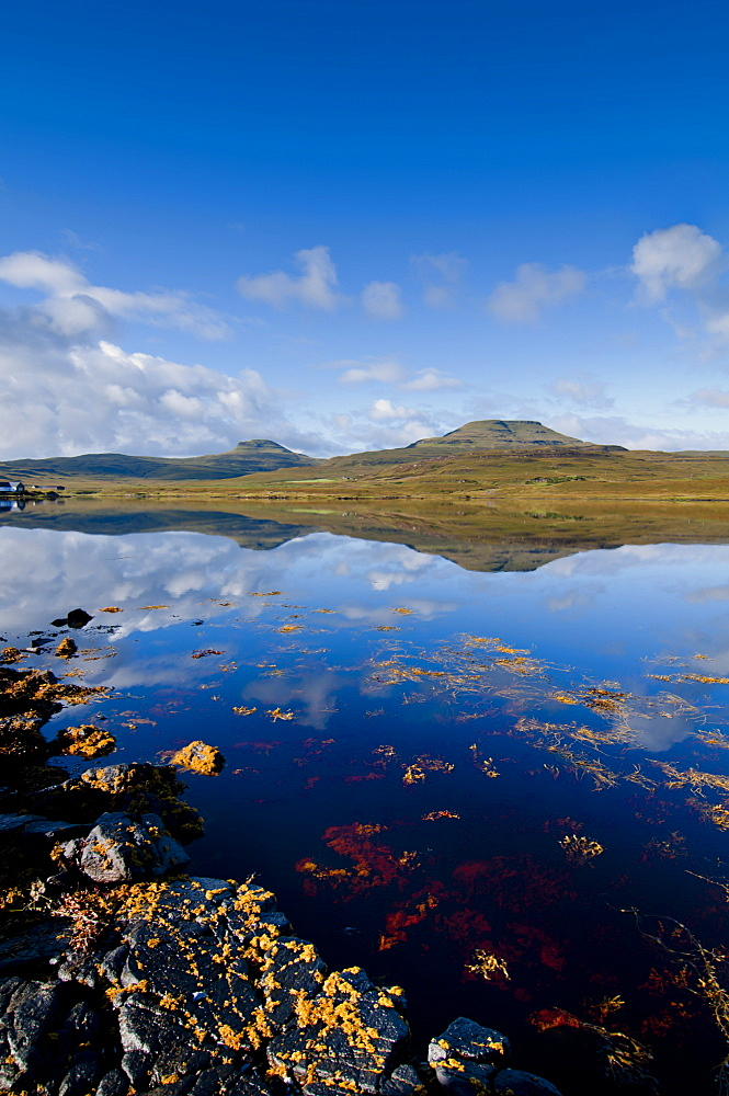 Craggy seascape of Loch Dunvegan on the Isle of Skye, with Macleod's Table in background., Isle of Skye, Inner Hebrides, Scotland, United Kingdom, Europe