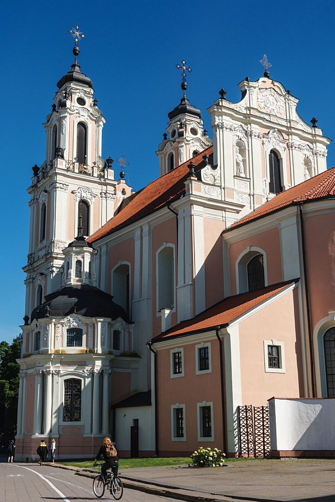 Cyclist passes by strawberry and cream Baroque Church of St Catherine, Old Town (UNESCO Wolrd Heritage Site), Vilnius, Lithuania - 450-4292