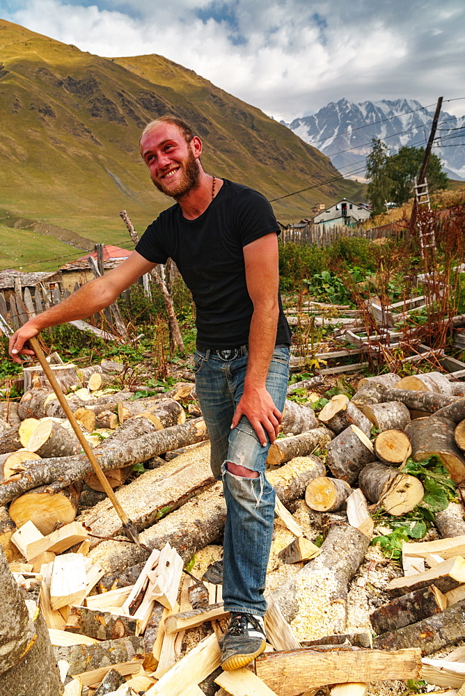 Woodcutter against Mount Shkhara, Georgia's highest peak, Upper Svaneti, UNESCO World Heritage Site, Georgia, Central Asia, Asia