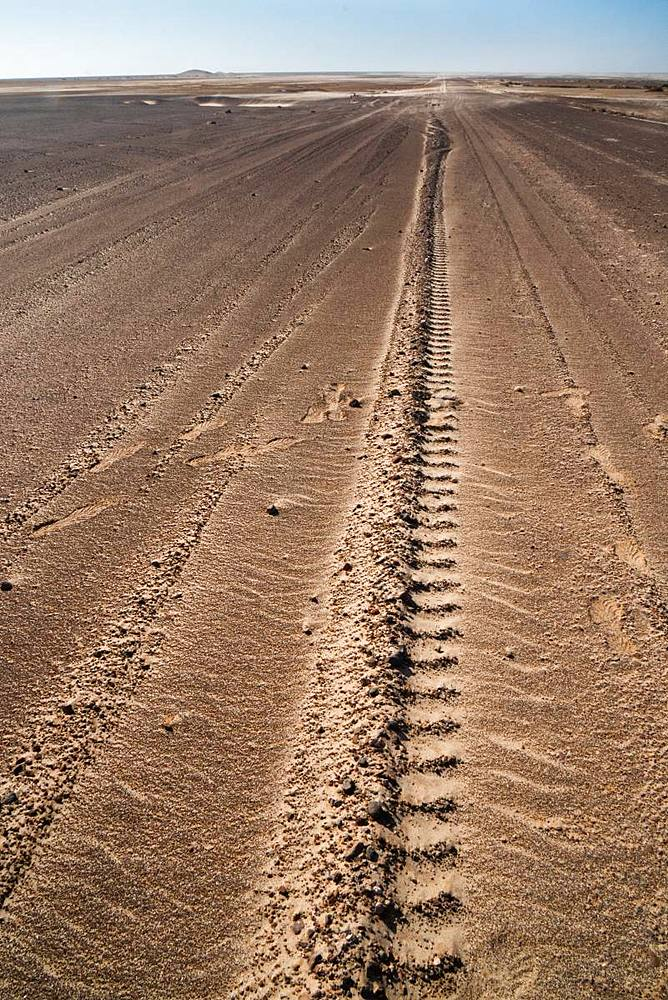 Tyre tracks delineate a seemingly endless straight road in Namib Desert near the infamous Skeleton Coast, Namibia, Africa - 450-4350