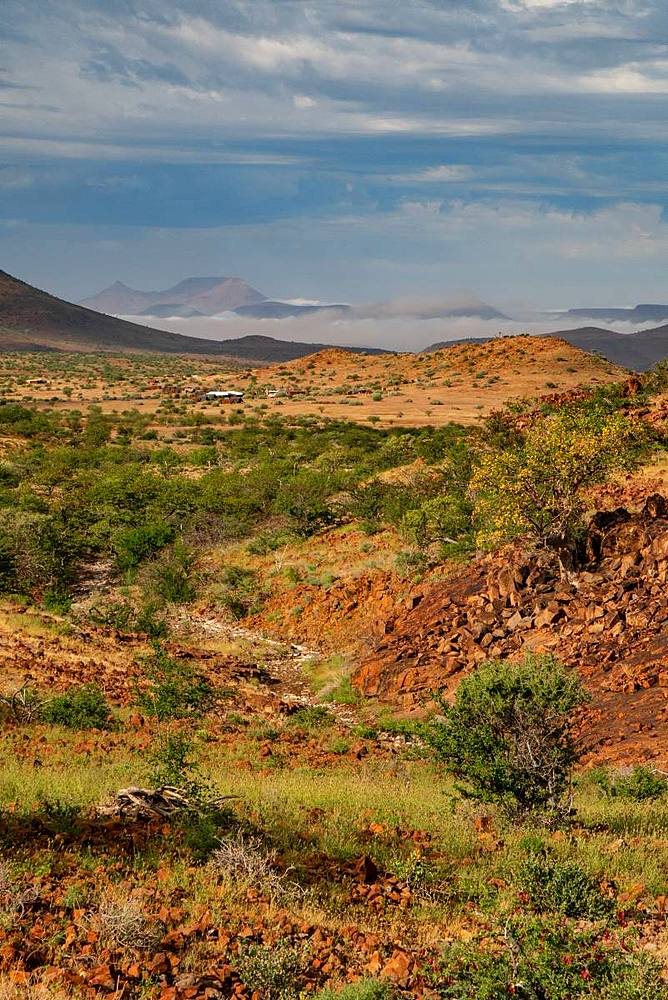 Colourful rocky landscape high up in the hills, with mountain camp in the background, Etendeka, Namibia