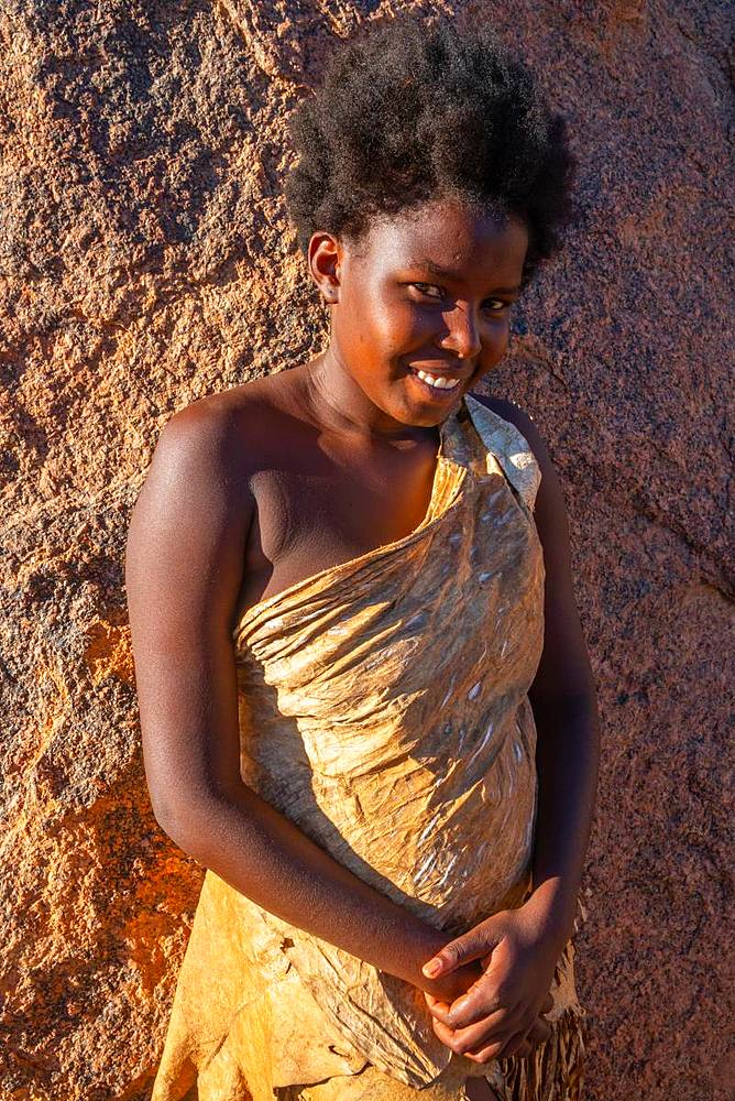 Portrait of woman resting against a rock in the sun at a Damara tribal village near Twyfelfontein, Namibia, Africa
