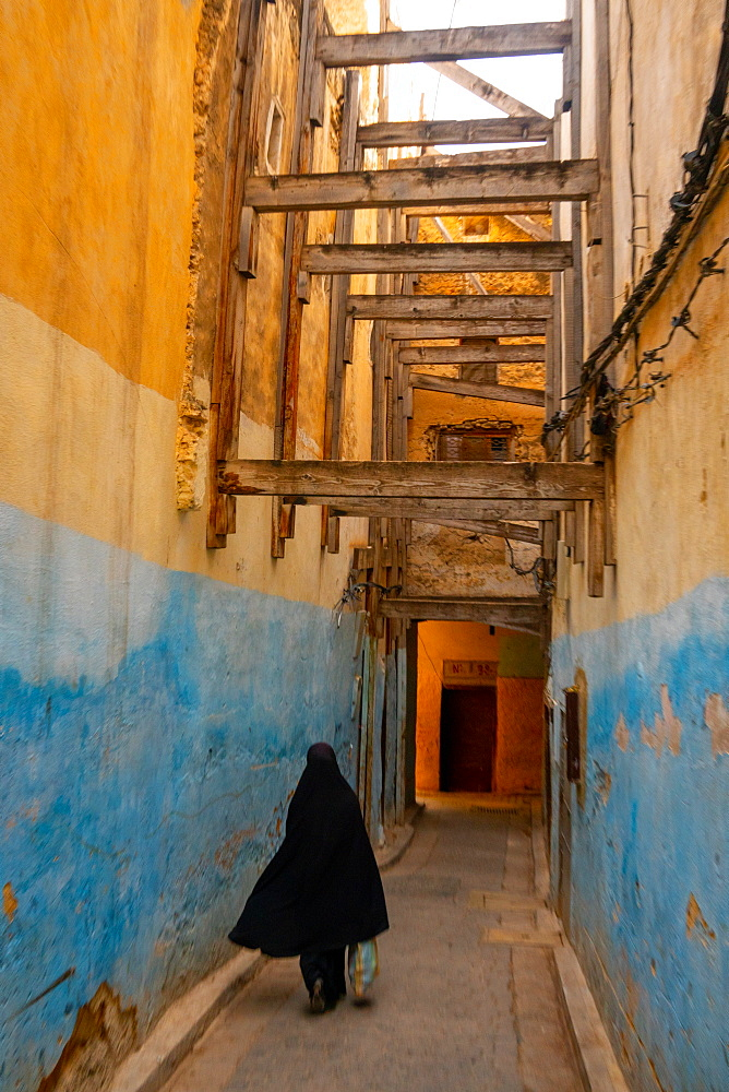 Woman in black traditional dress disappears down a colourful alleyway in the Old City (Medina) of Fez, Morocco, North Africa, Africa