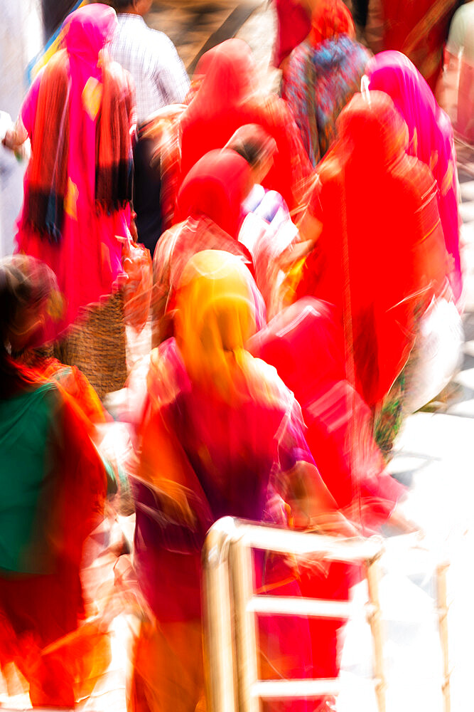 Brightly coloured saris (clothing) and veils, blurred in motion for effect, worn by women walking down towards the sacred lake.