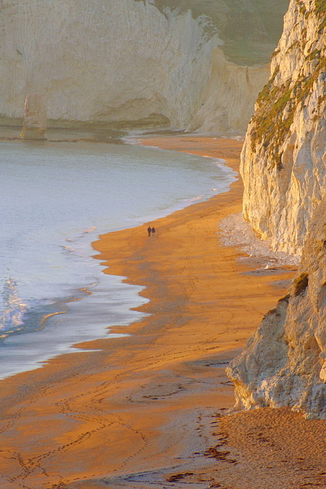 Couple walking on beach. Isle of Purbeck, Dorset, England UK