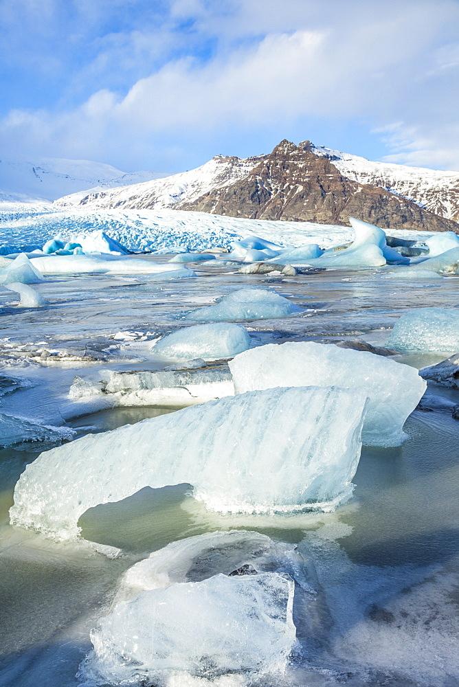 Frozen icebergs locked in the frozen waters of Fjallsarlon Glacier lagoon, South East Iceland, Iceland, Polar Regions