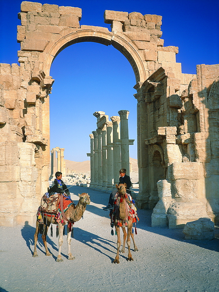 Syria, Palmyra Oasis, The Roman City Ruins, Gate Entering The 1200m Columnade Edging The Cardo (Main Road In The Roman Cities Center), Camel Riders On The Road