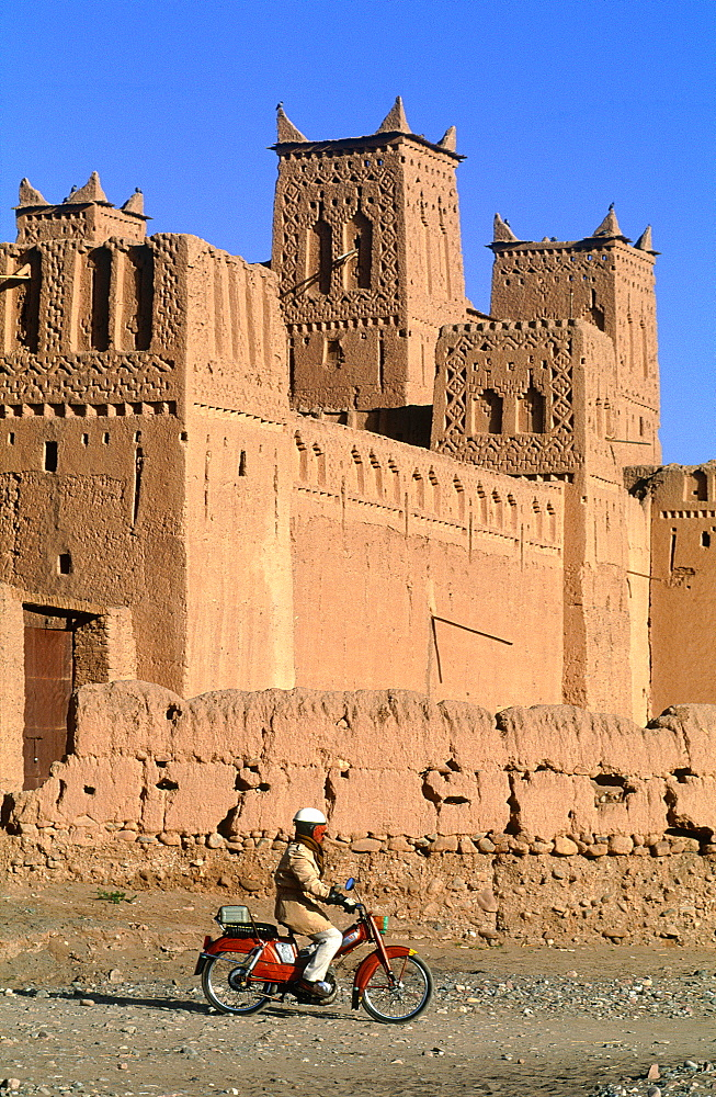 Morocco, South Atlas, Skoura Oasis, Amerhidil Kasbah (Adobe Fortress) Man On Moped Passing By