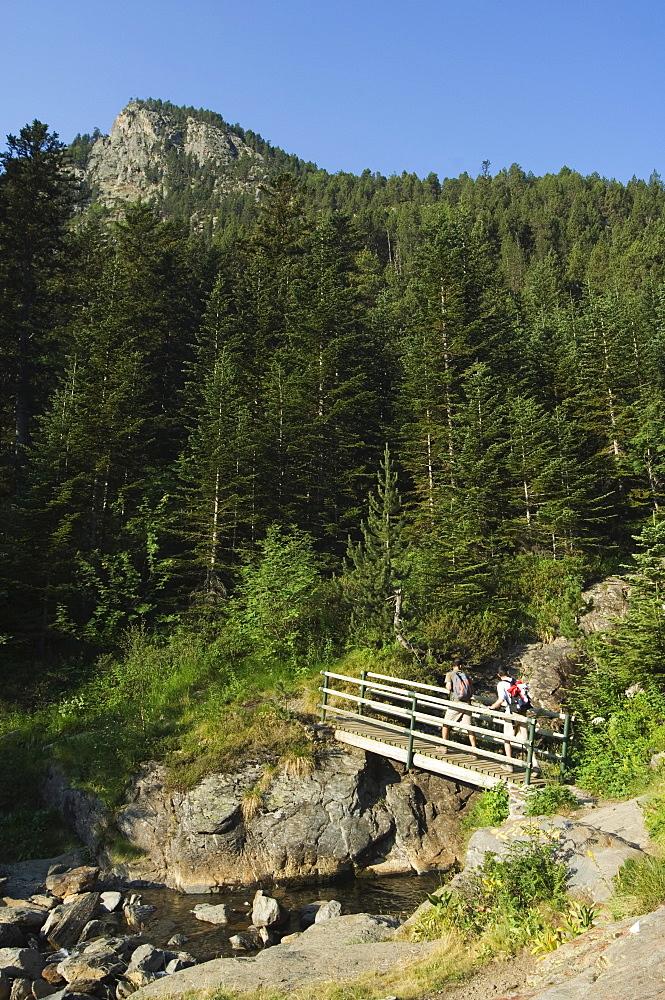 Hikers on bridge in hiking area of Pic de Coma Pedrosa, Parish of La Massana, Andorra, Pyrenees, Europe