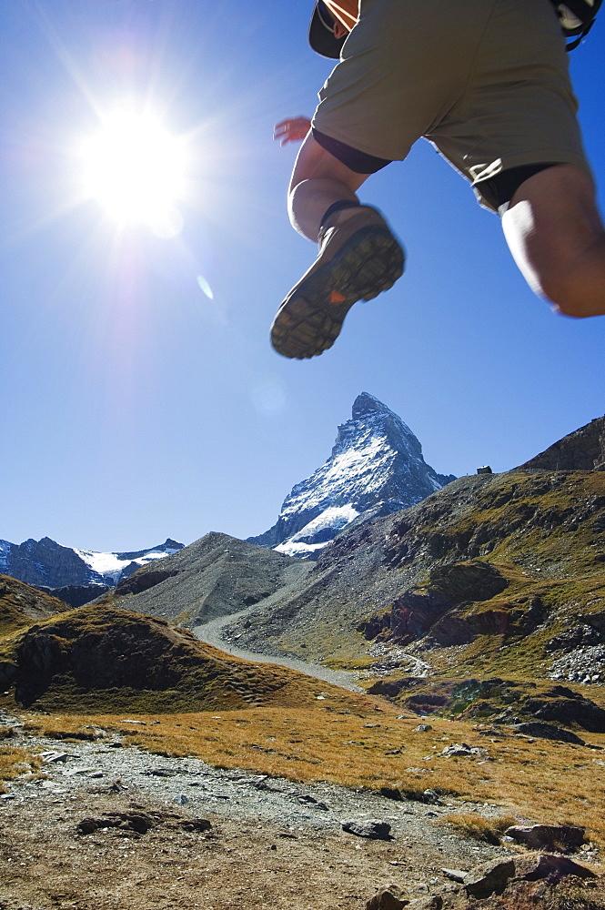 Hiker running on trail and the Matterhorn, 4477m,  Zermatt Alpine Resort, The Valais, Swiss Alps, Switzerland, Europe - 733-1568