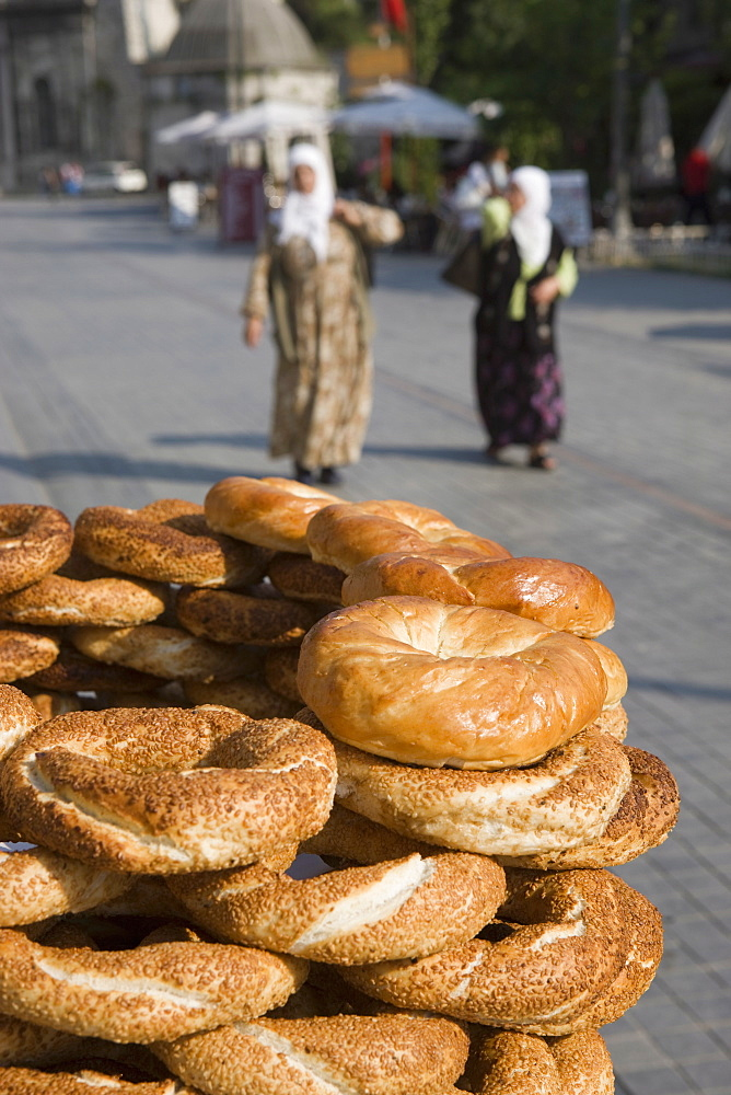 Traditional Turkish bagels with sesame seeds for sale, ladies in traditional costume in distance, Istanbul, Turkey, Europe