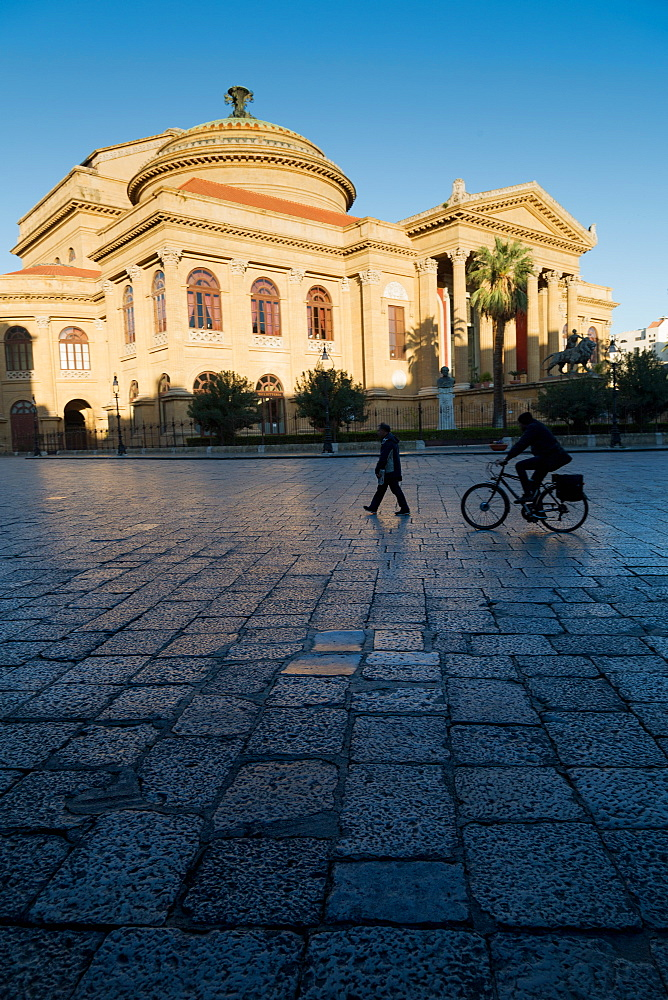 Cyclist and pedestrian passing Teatro Massimo in early morning light, one of the largest opera houses in Europe, Palermo, Sicily, Italy, Europe