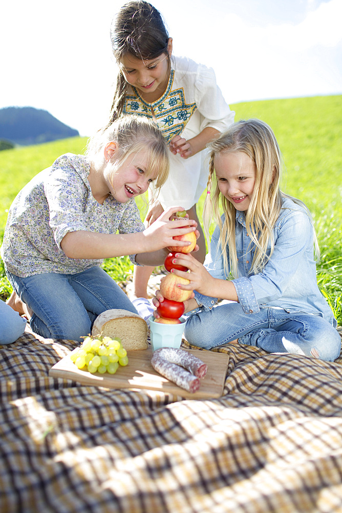 Girls On Countryside Picnic Trying To Balance Apples