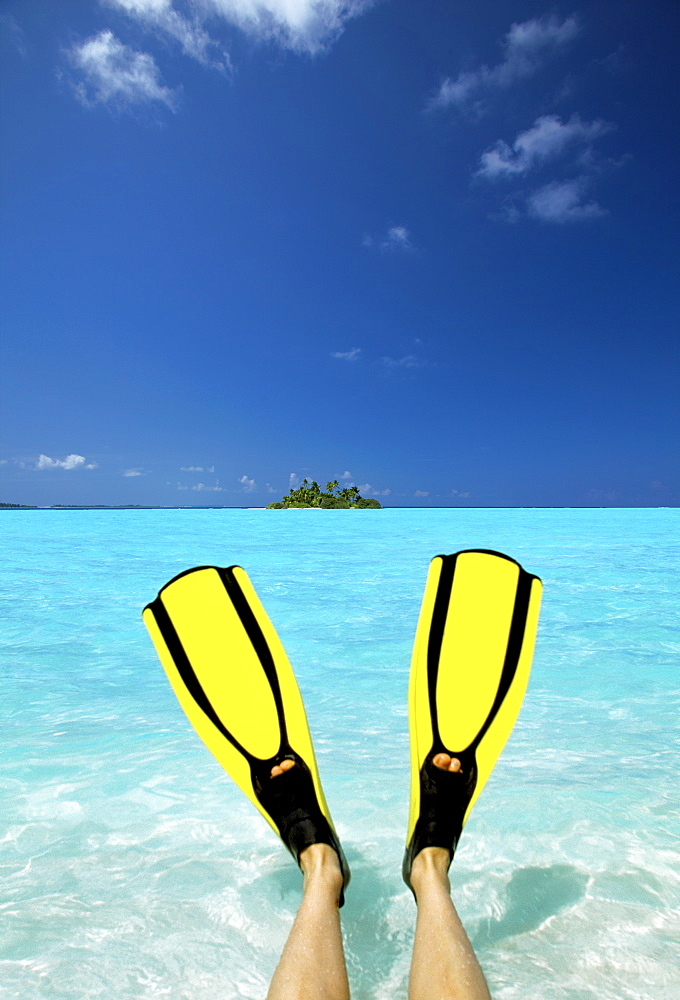 Tropical island and person wearing flippers sitting in sea, Maldives, Indian Ocean, Asia