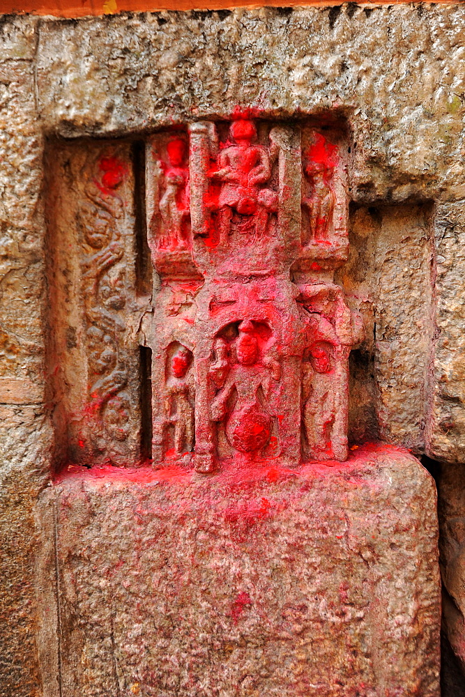 450 year old carvings of gods, blessed with red powder by pilgrims, in the walls of the Kamakhya temple, Gauhati, Assam