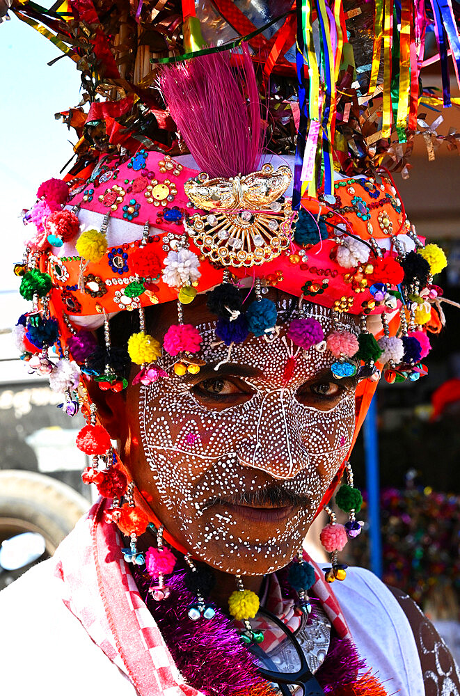Adavasi tribal man, face decorated and wearing ornate decorated headgear to celebrate Holi festival, Kavant, Gujarat