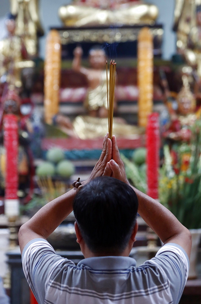Man praying to the Buddha holding incense sticks, Tay An temple, Chau Doc, Vietnam, Indochina, Southeast Asia, Asia - 809-7679