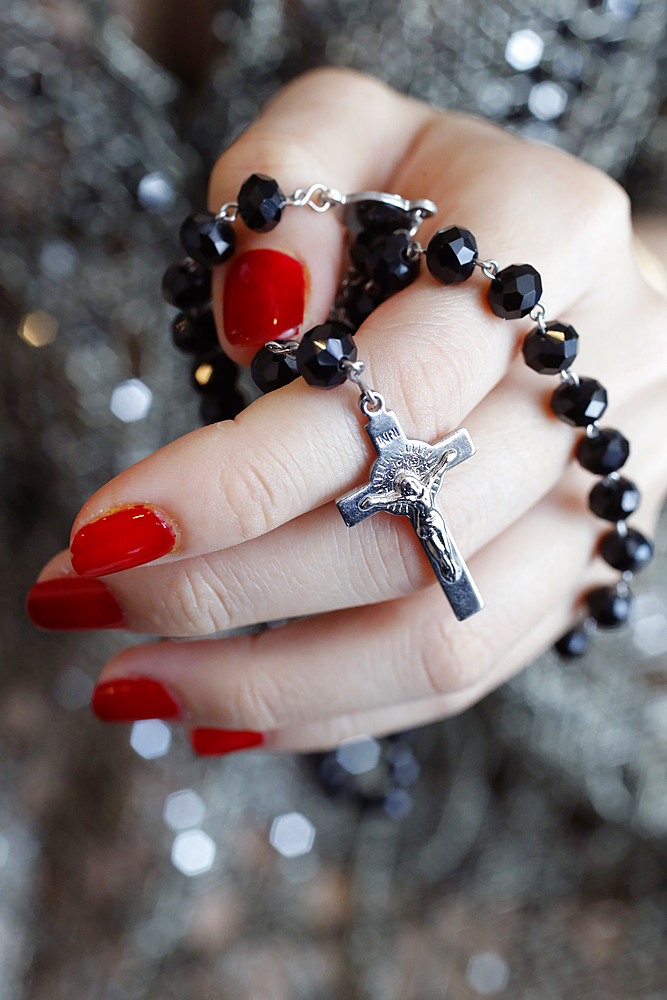 Catholic woman praying rosary beads and crucifix, Vietnam, Indochina, Southeast Asia, Asia