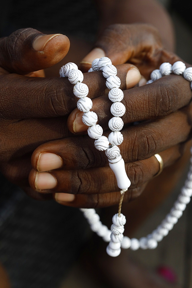 Close-up of hands of African Muslim man praying with Islamic prayer beads (tasbih), Togo, West Africa, Africa
