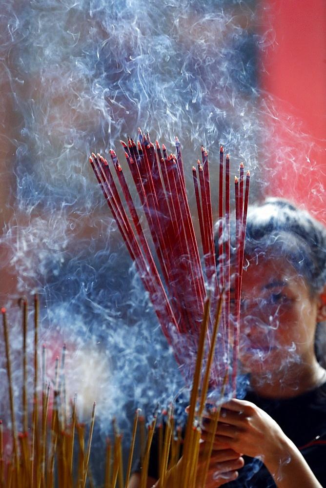 Woman praying with burning incense sticks, Ong Bon Pagoda, Taoist Temple, Ho Chi Minh City, Vietnam, Indochina, Southeast Asia, Asia