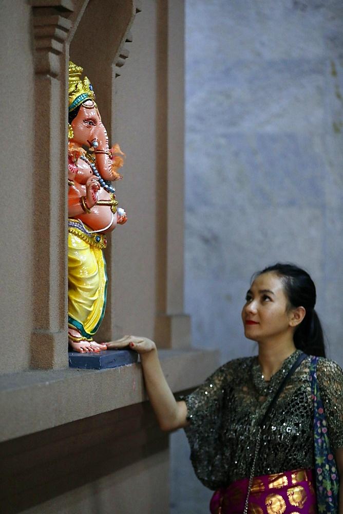 Woman praying to Hindu deity Ganesh statue, Sri Mahamariamman Hindu Temple, Kuala Lumpur, Malaysia, Southeast Asia, Asia