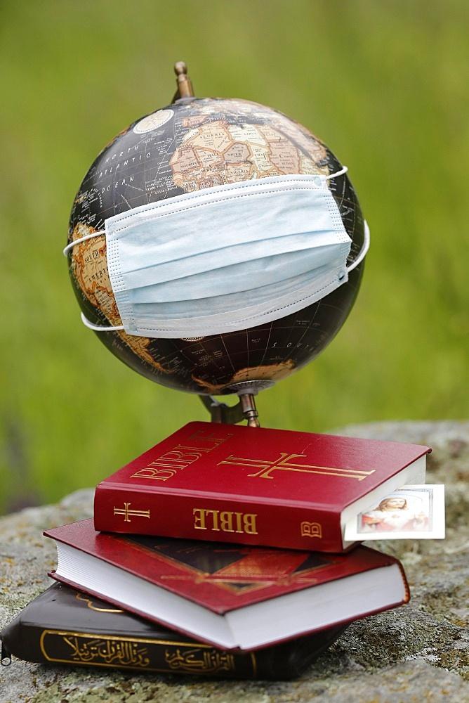 Coronavirus (Covid-19), global pandemic, World map with surgical mask and Bible, Koran and Torah, Interreligious dialogue, France, Europe