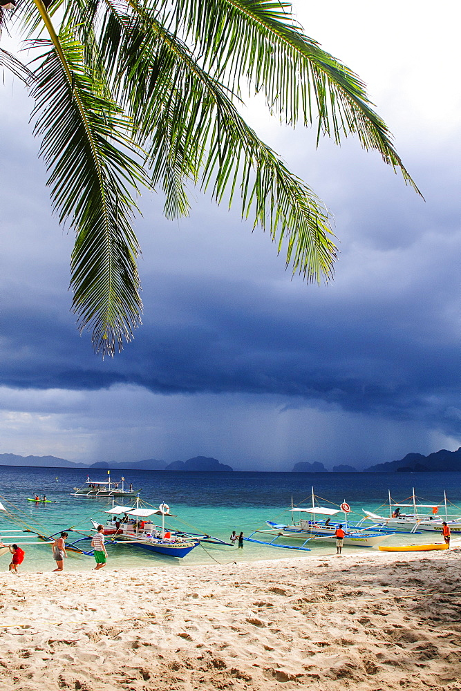 Outrigger boats before a strom anchoring on a sandy beach  in  the Bacuit archipelago, Palawan, Philippines, Southeast Asia, Asia
