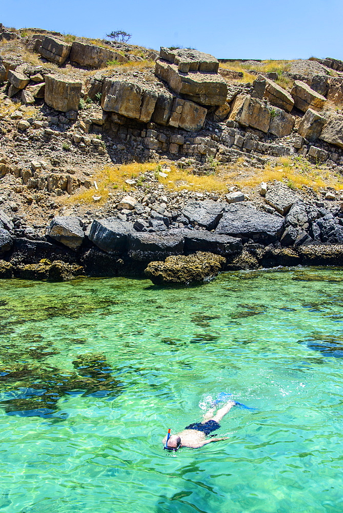 Man snorkelling in the clear waters of Telegraph Island in the Khor ash-sham fjord, Musandam, Oman, Middle East