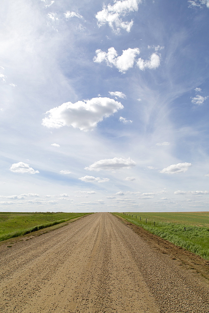 Clouds and bue sky over a dirt track in the Badlands of Alberta, near Drumheller, in Canada