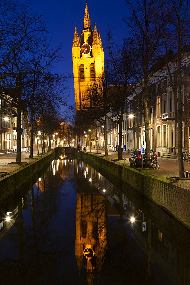 The Oude Kerk's leaning tower (Oude Jan) (Scheve Jan) reflected at night in the Oude Delft canal in Delft, South Holland, The Netherlands, Europe