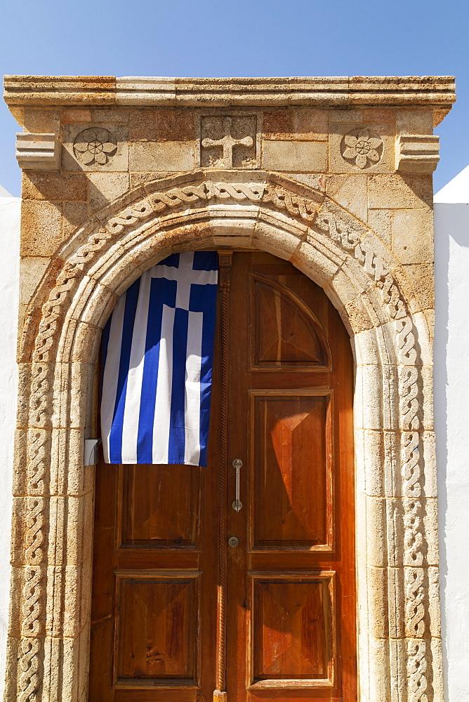 A Greek flag hangs under the stone archway in the doorway of one of the captain's houses of Lindos on Rhodes, Dodecanese, Greek Islands, Greece, Europe