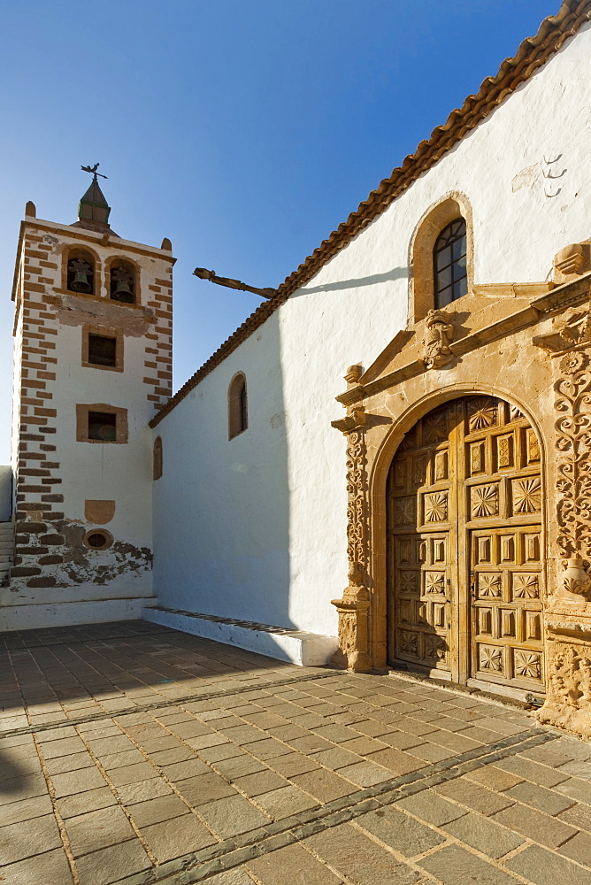 Door and belltower of the 17th century Santa Maria Cathedral in this historic former capital, Betancuria, Fuerteventura, Canary Islands, Spain, Europe