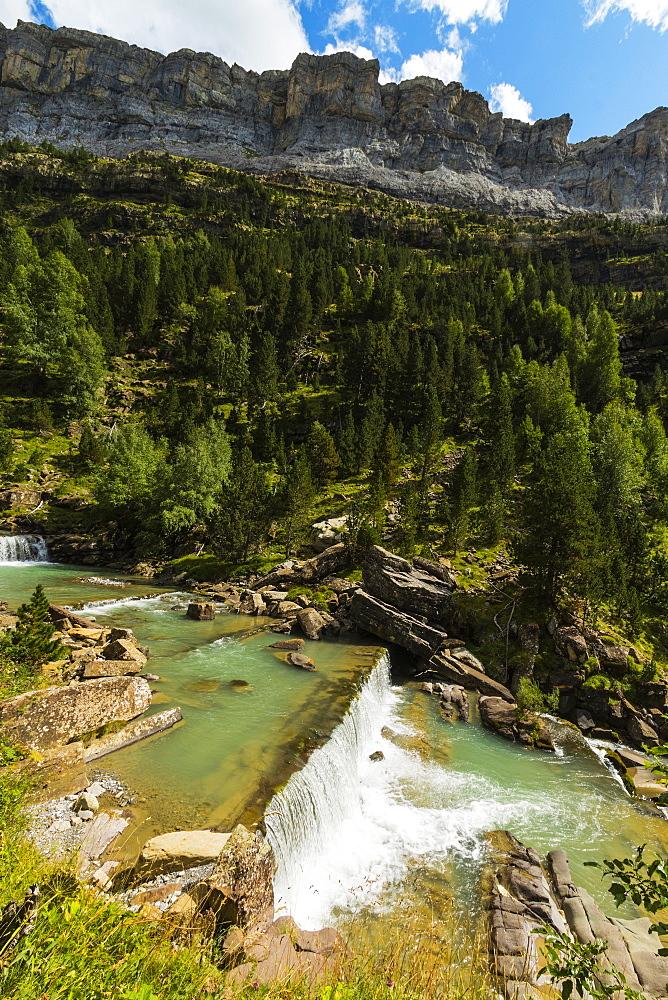 Sierra de las Cutas on the south rim above a Rio Arazas waterfall, Ordesa Valley. Ordesa National Park; Pyrenees; Aragon; Spain - 83-13021
