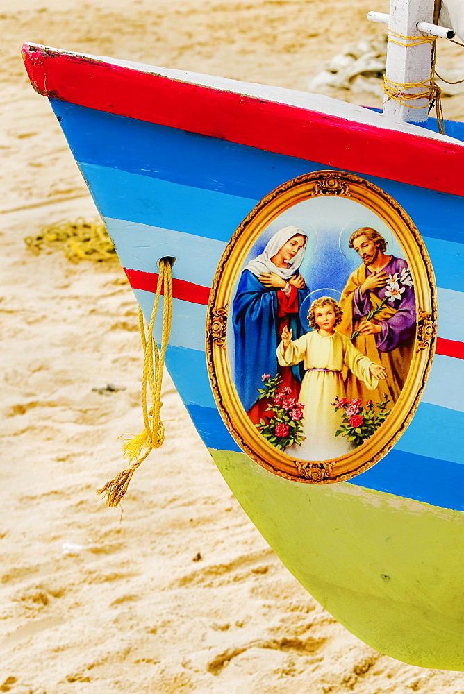 Colourful prow of fishing boat with Jesus, Mary, Joseph Christian picture on Marari Beach; Mararikulam, Alappuzha, Kerala, India