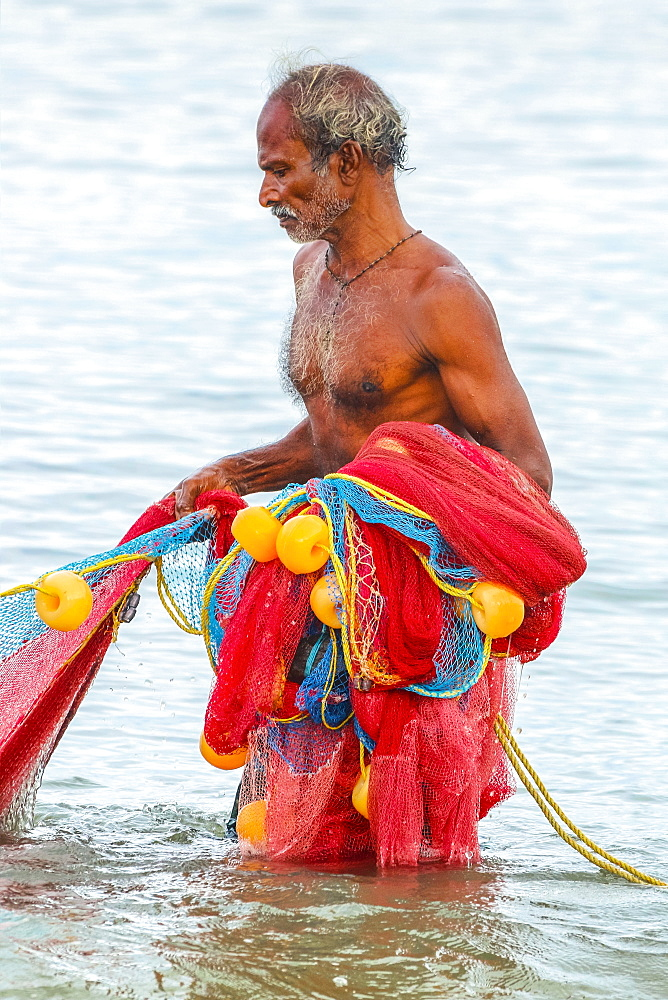 Fisherman retrieving large net to shore at popular Marari Beach; Mararikulam, Alappuzha (Alleppey), Kerala, India