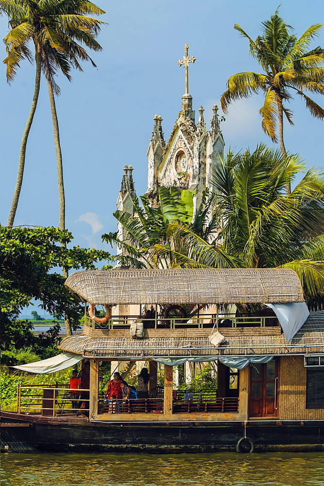 Old church with patinated facade & moored houseboat on a backwaters cruise visitor stop; Alappuzha (Alleppey), Kerala, India
